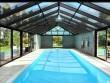 Une piscine grand format sous une véranda en aluminium