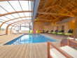 Une piscine semi-extérieure sous un abri télescopique en bois