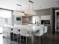 Trio bois, verre et pierre pour une cuisine avec îlot central