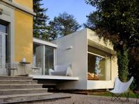 Une extension s'immisce entre un arbre et une maison bourgeoise