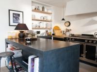 Une cuisine avec îlot et plan de travail en béton ciré