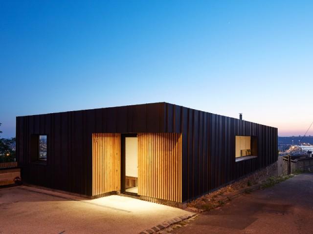 Une maison construite en pleine pente - Une maison en zinc noir posée sur un mur en brique