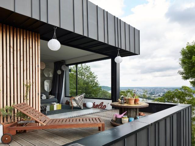 Une terrasse panoramique - Une maison en zinc noir posée sur un mur en brique