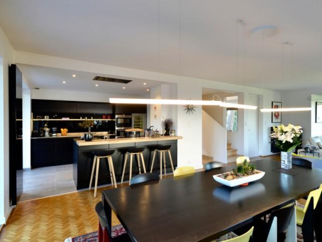 Une cuisine ouverte délimitée par un bar noir