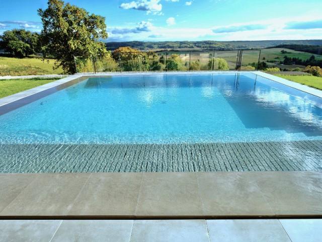 Une piscine miroir immerg e dans la campagne is roise for Caniveau pour piscine a debordement