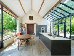 Extension maison : une véranda imbriquée entre trois bâtiments existants