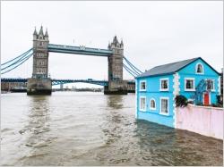 Une maison bleue flotte sur la Tamise