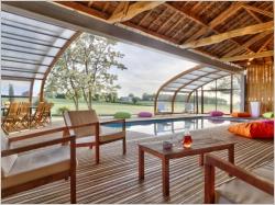 Un abri de piscine en bois ferme un hangar pour une piscine dedans/dehors