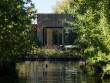 Une petite maison noire posée sur l'eau