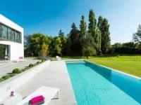 Une piscine se déverse sur un jardin verdoyant