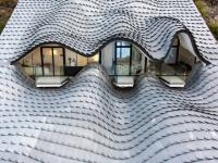 Une villa à flanc de falaise arbore une toiture en écailles de zinc