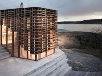 Une maison en bois polymère se dresse sur un plateau rocheux