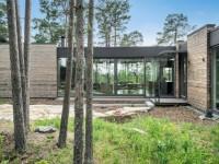 En Suède, une maison en bois se fond dans une forêt de pins