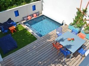 Un mini jardin avec terrasse et piscine à l'abri