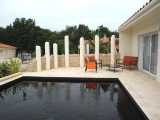 L'extérieur d'une villa remodelé autour d'une piscine noire