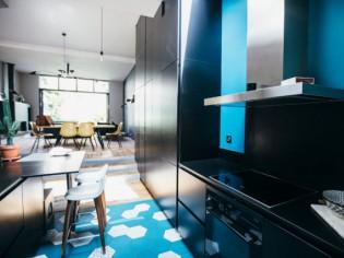 Une cuisine aménagée sous pente ose le noir mat