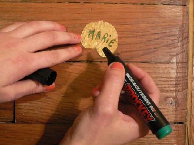 Ecrire les noms au marqueur sur la feuille dorée - Déco table Noël