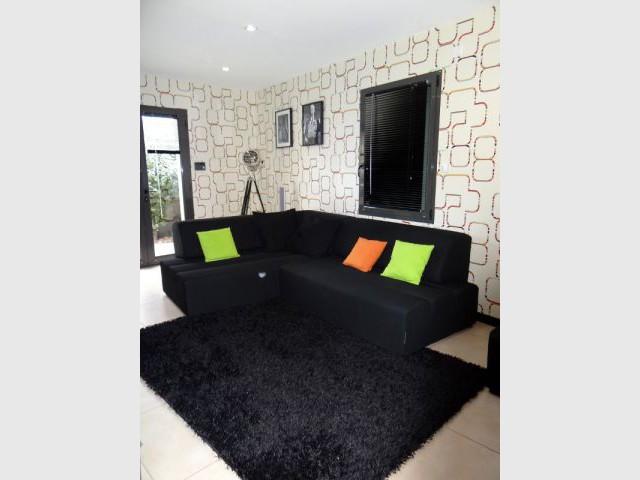 Canapé noir sur papier peint blanc - Reportage salon télé