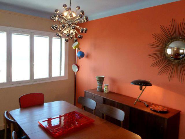 Salle à manger - Mur orange et suspension lumineuse - Appart fifties coloré