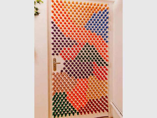 Une porte couverte de capsules colorées - Jardins de Babylone