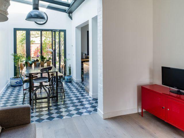 Une salle à manger sous une verrière - Une maison de ville au décor industriel