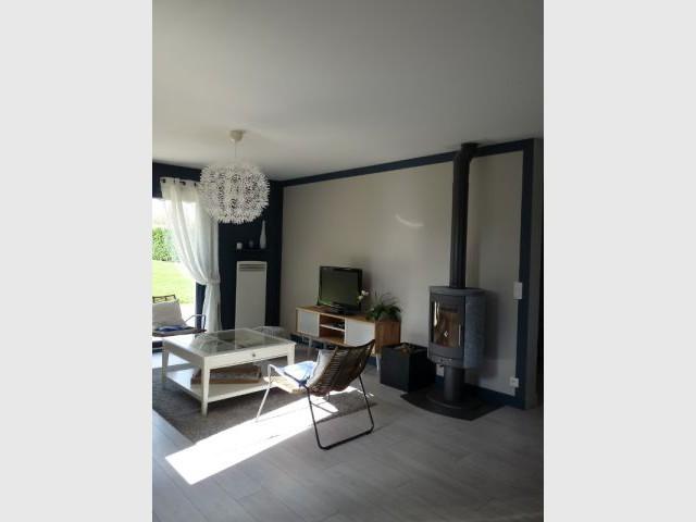 Un cadre de peinture insérant élégamment le poêle à bois - Un salon démodé retrouve fraîcheur et convivialité