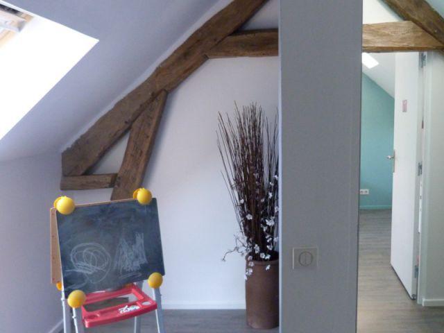 Des murs rampants en blanc associés à des poutres conservées - Un grenier inexploité rénové en chambre pour enfants