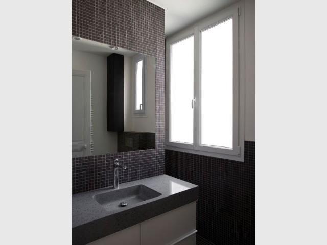 Une salle de bains graphique et spacieuse - Un meuble central décloisonne un appartement vétus