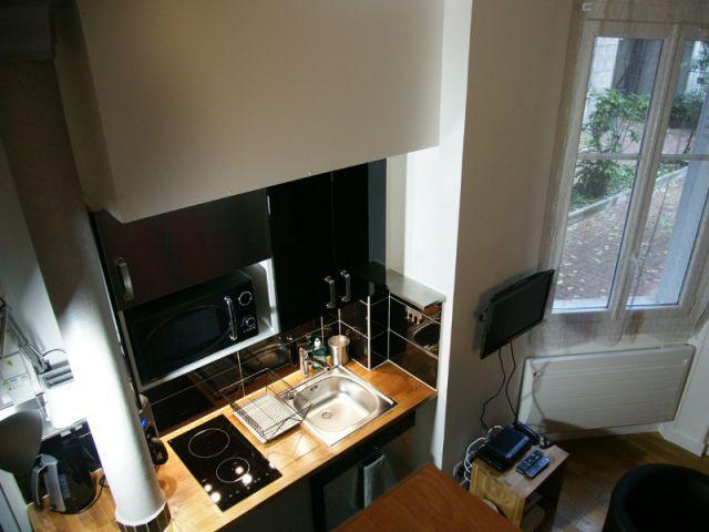 Une cuisine toute équipée associant une teinte noire et boisée - Loge de gardiens en studio moderne