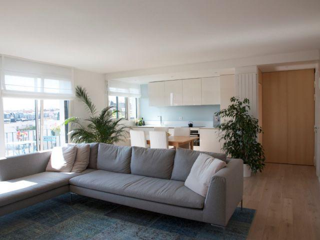 Une pièce à vivre qui associe salon, bibliothèque, cuisine et salle à manger - Des rangements sur-mesure pour gagner de la place