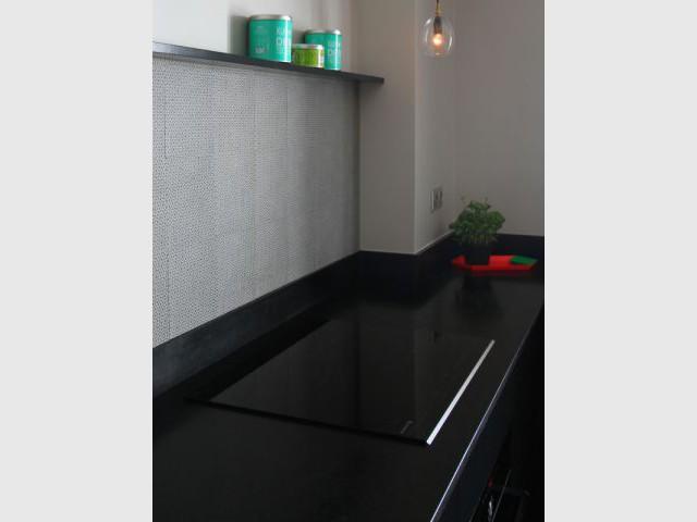 Des plaques de cuisson intégrées au granit noir  - Cuisine à vivre graphique et vive