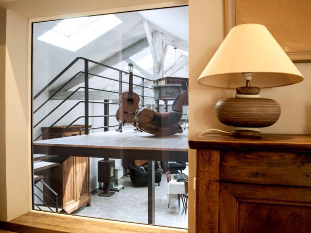 Une grande vitre qui relie visuellement les différents espaces du loft - Reconversion d'une ancienne papeterie en loft contemporain