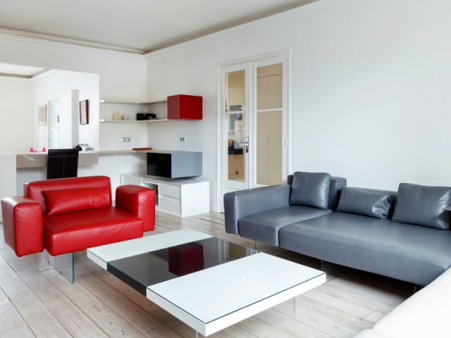Un fauteuil rouge comme seul élément coloré du coin salon - Un appartement fonctionnel et rafraichissant aux touches de couleurs pop