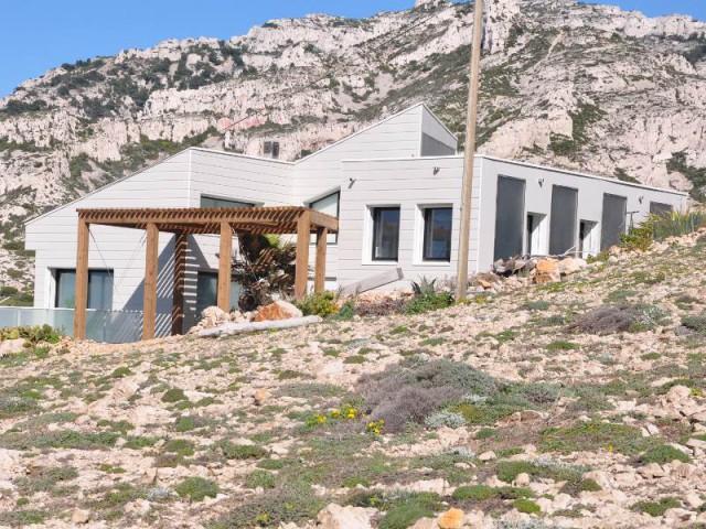 Des espaces de vie au même niveau que les extérieurs - Une villa cachée parmi les rochers au bord de la mer