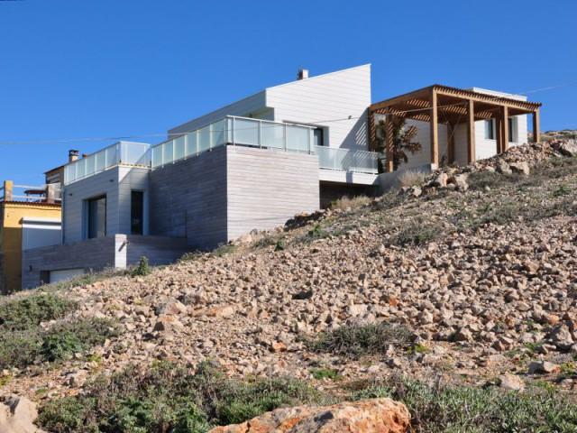 Un aspect cabanon pour une intégration parfaite dans le paysage local - Une villa cachée parmi les rochers au bord de la mer