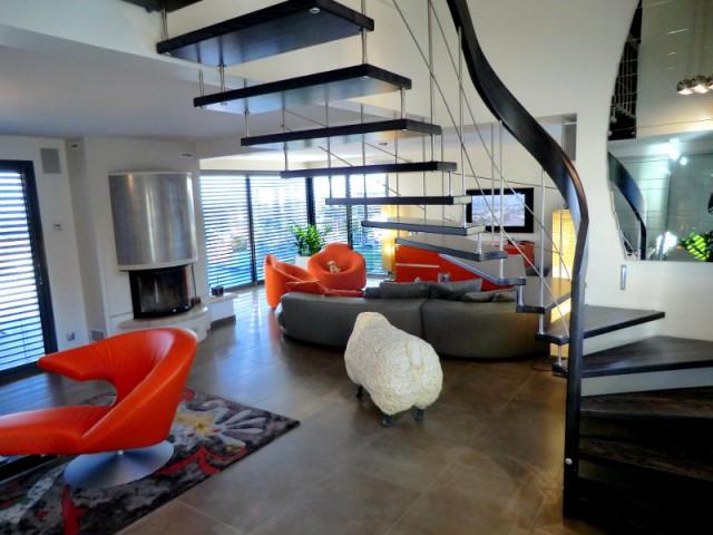 Un escalier suspendu au-dessus d'une pièce à vivre - Escalier gain de place