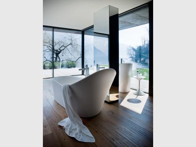 Une salle de bains avec un miroir de pied au centre - Une salle de bains ouverte sur l'extérieur