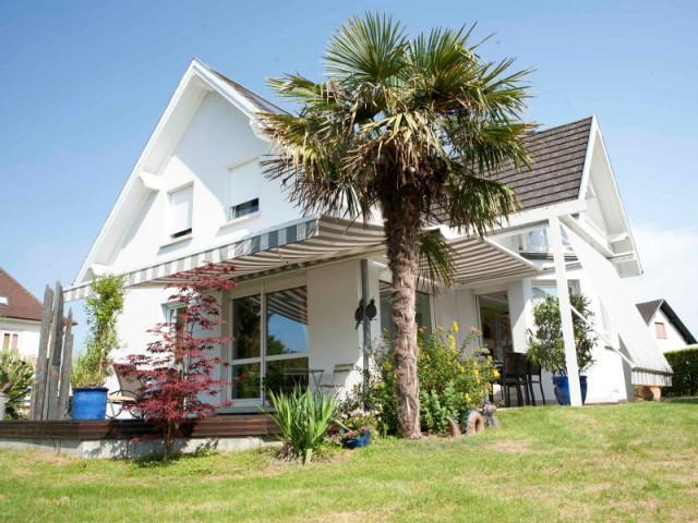 Des stores blanc et brun dans la continuité de la façade - Un store de terrasse en harmonie avec la maison