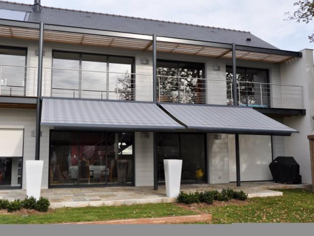 Des stores gris en camaïeu avec la toiture et la pergola - Un store de terrasse en harmonie avec la maison