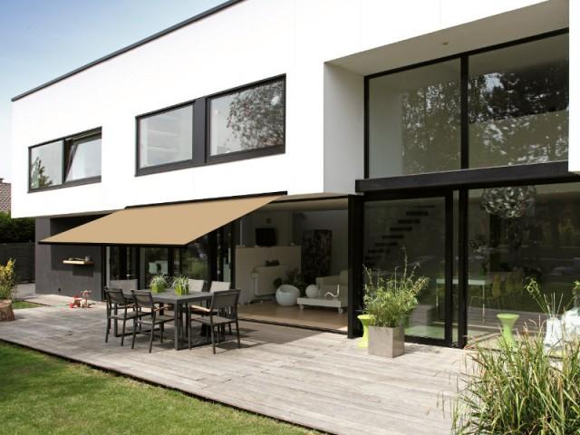 Un store beige raccord avec le sol du salon - Un store de terrasse en harmonie avec la maison