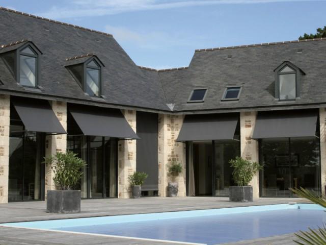 Des stores ardoise dans la continuité de la toiture - Un store de terrasse en harmonie avec la maison