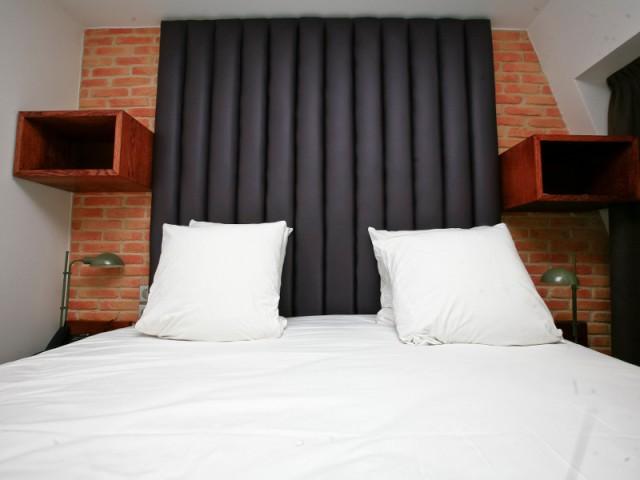Un parement en brique et des tables de chevet en lévitation pour une tête de lit atypique - Hôtel du Jeu de Paume à Versailles