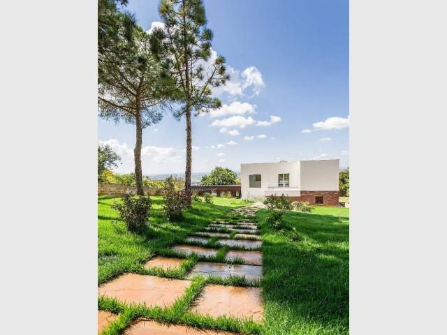 Un chemin de pierre qui mène à une maison cachée dans la nature - Courtyard House in Trapani by Studio 4e