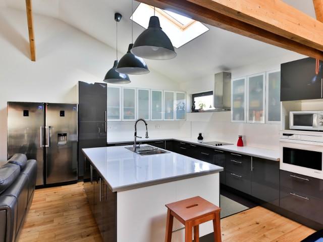 Une cuisine équipée et ouverte sur le salon - Un ancien hangar transformé en maison bois à Argentueil