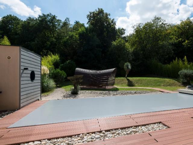 Une pergola en forme de vague - Une couverture de piscine dissimulée dans une terrasse paysagère