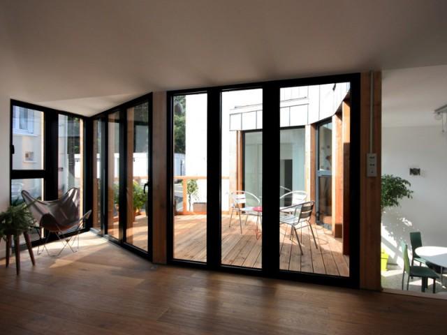 Un salon ouvert sur l'extérieur grâce à la terrasse - Rénovation, extension et surélévation à Nantes