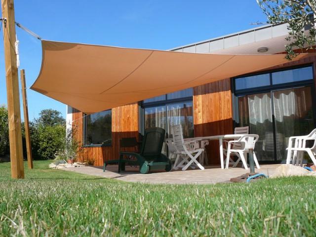 Un voile d'ombrage aux mâts en bois assortis à la maison - Voile d'ombrage