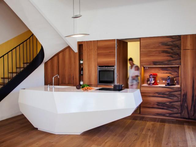 Une porte dissimulée cache le cellier et les toilettes - Une cuisine en noyer français et LG HiMacs