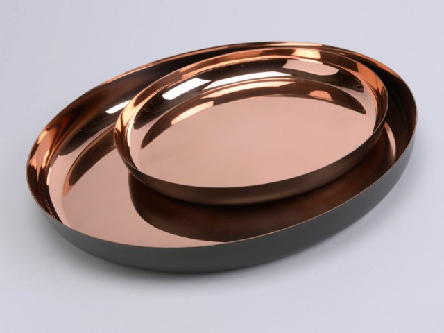 Sur la table basse, des plateaux noir et cuivre rosé - Tendance cuivre rosé