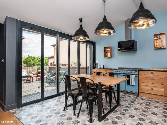 Des ouvertures toute hauteur comme une verrière intérieure - Bois brut et style industriel pour une cuisine ouverte sur une terrasse